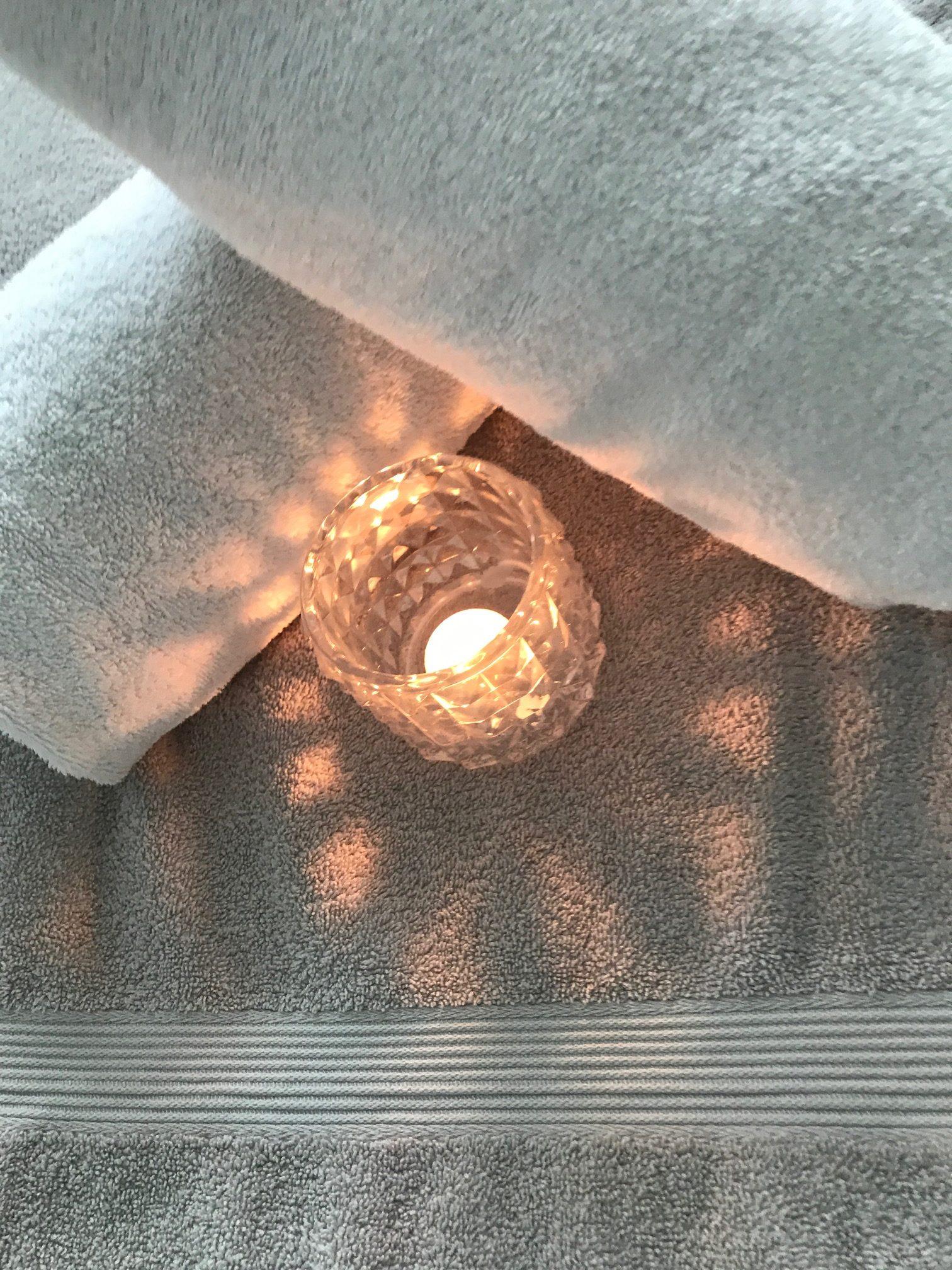 Ljuslykta och frottéhanddukar välkomnar på massagebänken
